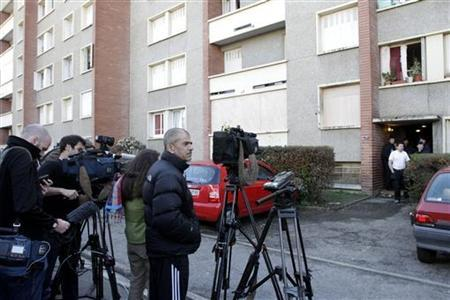 Members of the media work across the street from the boarded balcony and window of the ground floor flat at the five-storey apartment building where special forces police staged the assault on the gunman Mohamed Merah, in Toulouse March 23, 2012. REUTERS/Jean-Philippe Arles