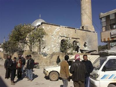 Residents are seen near a damaged mosque after heavy shelling by government forces in Sermeen, near the northern city of Idlib March 24, 2012. REUTER/Shaam News Network/Handout