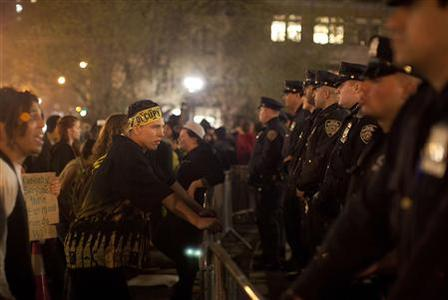 A man affiliated with the Occupy Wall Street Movement faces police officers after barricades were placed around Union Square in New York March 22, 2012. More than 100 protesters from the reawakened Occupy Wall Street movement were ejected from Union Square Park early Wednesday after a standoff with police resulted in six arrests. REUTERS/Andrew Kelly