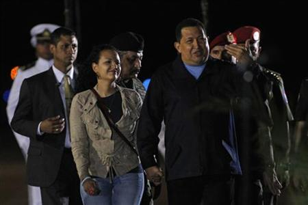 Venezuelan President Hugo Chavez walks with his daughter Rosa Virginia during his departure to La Habana, Cuba, where he will begin his radiation therapy sessions, at the Maiquetia Airport in Caracas March 24, 2012. REUTERS/Gil Montano