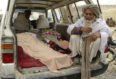 An Afghan man sits next to the covered bodies of people who were killed by coalition forces in Kandahar province in this March 11, 2012 file photo. REUTERS/Ahmad Nadeem/Files