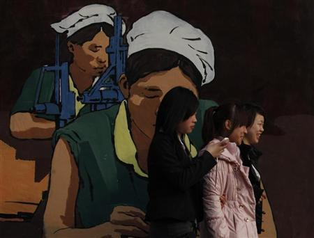 Women walk past an illustration of factory workers near an industrial park in Shenzhen February 13, 2012. REUTERS/Bobby Yip