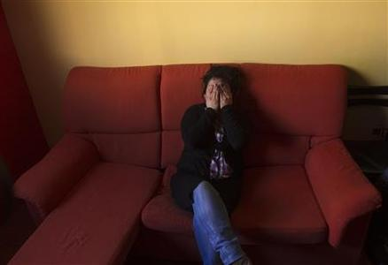 Kelly Herrera covers her face as she sits in the main room of her home after learning that her eviction had been suspended in Madrid in this March 13, 2012 file photo. REUTERS/Sergio Perez