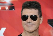 "Judge Simon Cowell poses for photographers following a news conference for the television show ""The X Factor"" held in Los Angeles December 19, 2011. REUTERS/Phil McCarten"