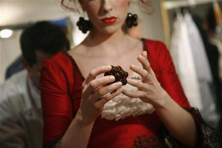 A model puts on a chocolate accessory backstage before the 9th Annual Chocolate Fashion Show in New York November 9, 2006. REUTERS/Eric Thayer (UNITED STATES)