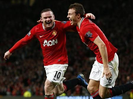 Manchester United's Wayne Rooney (L) celebrates his goal against Fulham with Jonny Evans during their English Premier League soccer match at Old Trafford in Manchester, northern England, March 26, 2012. REUTERS/Phil Noble