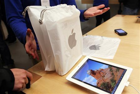 An employee presents purchased new iPads to a customer at the Apple flagship retail store in San Francisco, California in this March 16, 2012, file photo. REUTERS/Robert Galbraith/Files