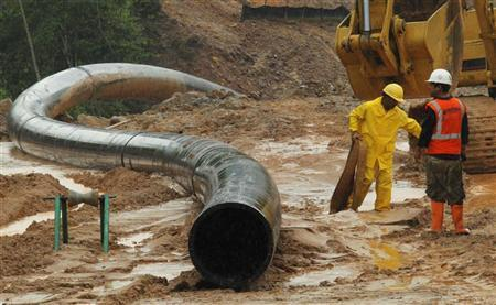 Members of Canadian company Barrick Gold work on the water dam affected by rains in Cotui May 30, 2011. REUTERS/Eduardo Munoz