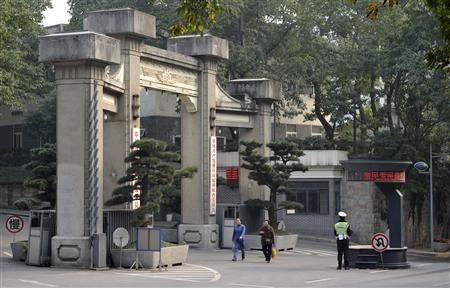 Pedestrians walk past as a policeman stands guard at the entrance to the Chongqing Municipal Government building in Chongqing municipality, March 15, 2012. REUTERS/Stringer