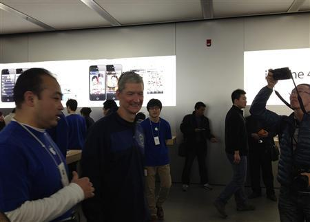 Apple CEO Tim Cook (2nd L) talks to employees at an Apple store in central Beijing, March 26, 2012. REUTERS/Stringer