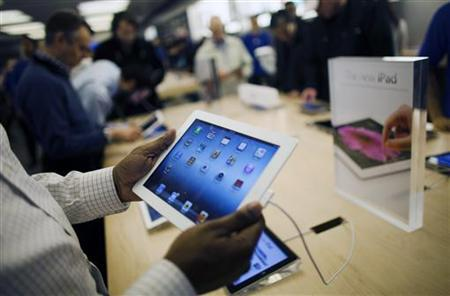 Customers look at the new iPad at the Apple Store in the Eaton Centre shopping mall in Toronto, March 16, 2012. REUTERS/Mark Blinch/Files