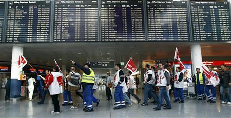 Globe Ground ground personnel march below a flight information board during a wage strike by Globe Ground ground personnel at Munich's international airport March 27, 2012. REUTERS/Michael Dalder