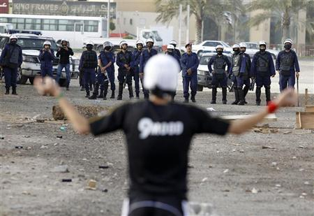 A rock-wielding anti-government protester confronts riot police during clashes in Budaiya west of Manama March 26, 2012. REUTERS/Hamad I Mohammed