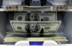 Счетчик банкнот считает доллары в банке в Берне, 15 августа 2011 г. Доллар опустился до минимального уровня за четыре недели к валютной корзине после выступления главы ФРС Бена Бернанке, указавшего на сохранение мягкой политики центробанка. REUTERS/Pascal Lauener