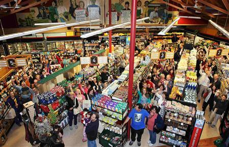 Customers line the aisles and hold up their money as they participate in a ''cash mob'' at a small locally owned organic store called Nature's Bin, in Lakewood, Ohio March 24, 2012. REUTERS/Aaron Josefczyk