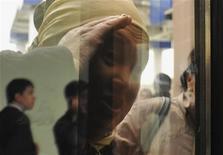 Женщина, стремящаяся попасть в помещение, где проходит открытый процесс над обвиняемыми в беспорядках в Жанаозене, смотрит из-за окна импровизированного зала суда в одном из общественных зданий в Актау, Казахстан 27 марта 2012. Разгневанные родственники обвиняемых во вторник ворвались в здание суда в Казахстане незадолго до начала процесса, посвященного кровопролитию в Жанаозене, которое разрушило имидж стабильности богатого нефтью государства в Центральной Азии. REUTERS/Vladimir Tretyakov