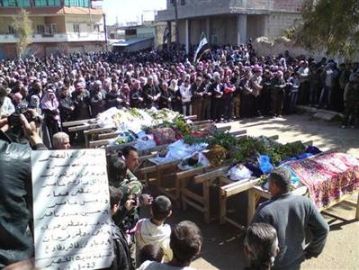 Syrians attend a mass funeral for people whom anti-government protesters said were killed by the shelling in Al Qasseer city, near Homs, March 23, 2012. REUTERS/Shaam News Network/Handout