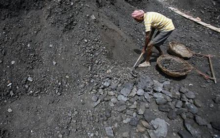 A worker shovels coal at a wholesale coal shop on the outskirts of Agartala, March 23, 2012. REUTERS/Jayanta Dey