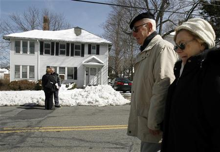 An auctioneer and a bidder (L) discuss a foreclosed home in Newton, Massachusetts as local residents (R) walk past March 19, 2007. REUTERS/Brian Snyder