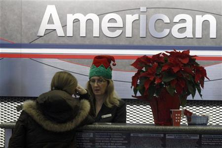 An American Airlines ticket agent checks in a passenger at O'Hare International Airport in Chicago December 23, 2011. REUTERS/Frank Polich