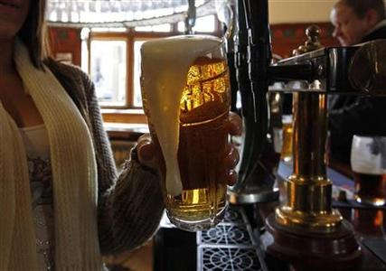 A barmaid pours a pint of beer at The Builders Arms pub in east London in this February 2, 2012 file photograph. REUTERS-Eddie Keogh