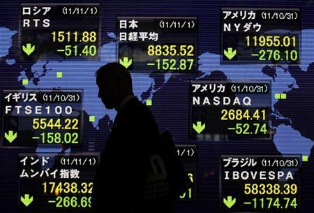 A man walks past an electronic board displaying falls in market indices from around the world outside a brokerage in Tokyo November 1, 2011. REUTERS/Yuriko Nakao