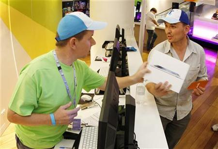 Construction manager David Tarasenko (R) purchases the first new iPad from a store in Sydney moments after midnight March 16, 2012. REUTERS/Tim Wimborne