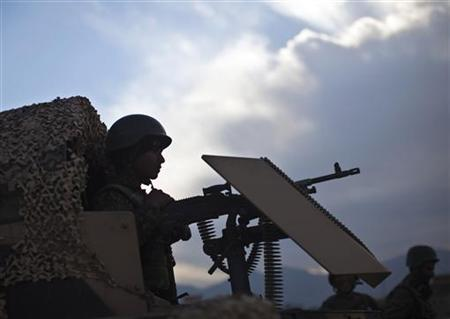 An Afghan National Army soldier mans a machine gun atop a military vehicle near the site where a suicide bomber was killed near the location of the Loya Jirga, or the traditional assembly, in Kabul November 14, 2011. REUTERS/Ahmad Masood/Files