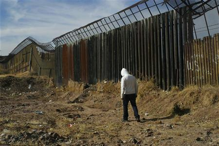 A young man walks next to the border fence between Mexico and the United States, in Nogales, January 6, 2011. REUTERS/Alonso Castillo