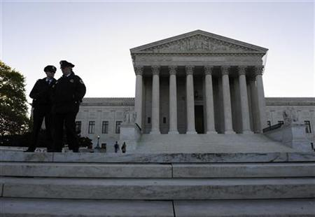 Police officers stand on the front steps on the first day of legal arguments over the Patient Protection and Affordable Care Act at the Supreme Court in Washington March 26, 2012. REUTERS/Jonathan Ernst
