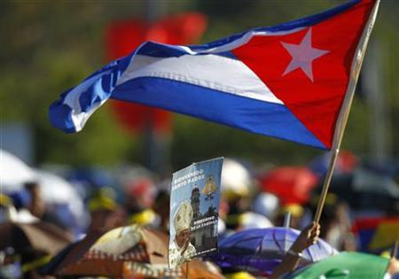 A person waves a Cuban flag while a sign showing Pope Benedict XVI is seen in the foreground, as people wait at Revolution Square in Havana March 28, 2012. REUTERS/Jorge Silva