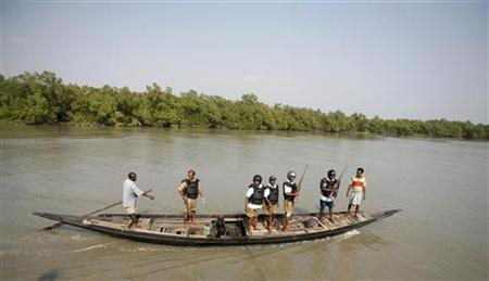 Indian forest guards and workers travel on a boat to collect statistics related to tigers during a week-long tiger census in the core area of Sundarbans Tiger Reserve, about 130 km south of Kolkata March 4, 2010. REUTERS/Parth Sanyal/Files