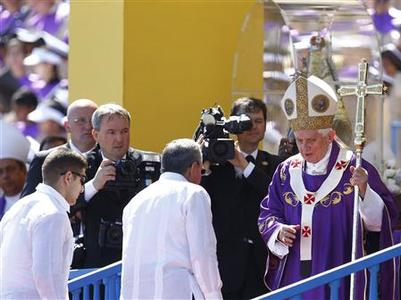 Cuba's President Raul Castro (C, back to camera) walks up the stage to greet Pope Benedict XVI after a mass at Revolution Square in Havana March 28, 2012. REUTERS/Jorge Silva
