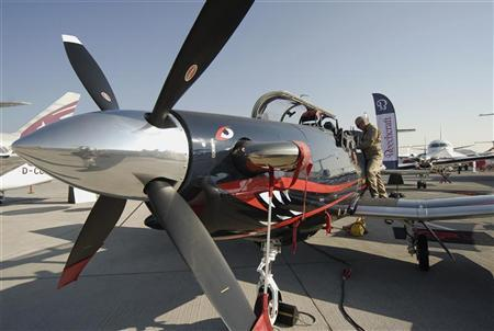 A pilot stands by his plane, a Hawker Beechcraft T-6C Texan II, during the second day of the Dubai Airshow November 14, 2011. REUTERS/Nikhil Monteiro