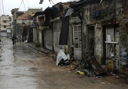 A man rides his bike past damaged buildings in the old Homs city in northern Syria March 28, 2012. REUTERS/Karam Karam