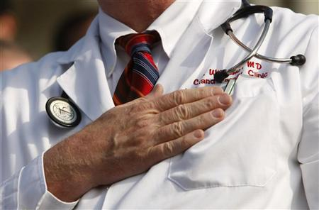 A doctor puts his hand over his chest during a ''House call'' rally against proposed healthcare reform legislation at the Capitol in Washington November 5, 2009. REUTERS/Kevin Lamarque