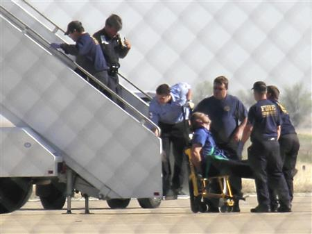 A JetBlue pilot captain Clayton Osbon, is removed from the plane after erratic behavior forced the crew to land in Amarillo, Texas, March 27, 2012. Osbon, who caused a disturbance on board JetBlue flight 191 from New York to Las Vegas, forcing the plane to make an emergency landing in Texas, has been suspended while the FBI investigates the incident, the airline said on March 28, 2012. REUTERS/Steve Miller/The Reporters Edge (UNITED STATES - Tags: TRANSPORT DISASTER HEALTH TPX IMAGES OF THE DAY)