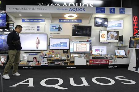A man walks past Sharp's television sets at an electronic shop in Tokyo March 19, 2012. REUTERS/Kim Kyung-Hoon
