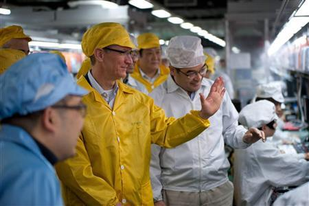 Apple Chief Executive Officer Tim Cook (2nd L) talks to employees as he visits the iPhone production line at the newly built Foxconn Zhengzhou Technology Park, Henan province in this March 28, 2012 handout photo. REUTERS/Apple/Handout