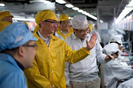 Apple Chief Executive Officer Tim Cook (2nd L) talks to employees as he visits the iPhone production line at the newly built Foxconn Zhengzhou Technology Park, Henan province in this March 28, 2012 handout photo. REUTERS/Apple/Handout CLIENTS