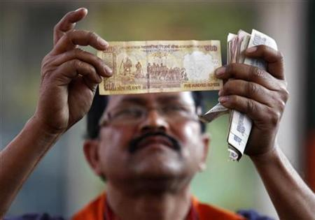 A worker at a fuel station checks a 500 Indian rupee note after filing a vehicle with fuel in Kolkata February 3, 2011. REUTERS/Rupak De Chowdhuri/Files