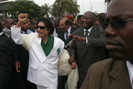 Libyan leader Muammar Gaddafi (L) is accompanied by Ivory Coast's President Laurent Gbagbo (R) during a welcoming ceremony upon his arrival at Felix Houphouet Boigny airport, outside Abidjan, at the start of a two-day visit to Ivory Coast June 27, 2007. REUTERS-Thierry Gouegnon-Files
