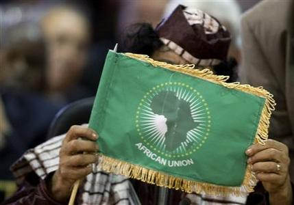 Libya's leader Muammar Gaddafi looks at a flag during the plenary session at the Africa-South America Summit in Margarita Island September 27, 2009. REUTERS-Carlos Garcia Rawlins-Files