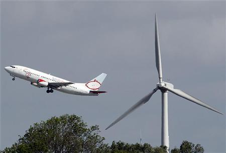 A BMI Baby aircraft takes off over a wind turbine at East Midlands Airport, central England May 10, 2011. REUTERS/Darren Staples