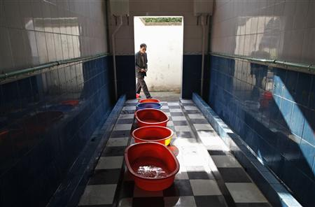 A man walks into a primary school toilet where containers are placed to collect urine passed out by boys, in Dongyang, Zhejiang province March 26, 2012. REUTERS/Aly Song