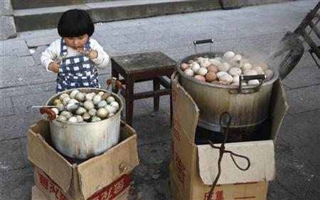 A girl looks at a pot of regular hard-boiled eggs, next to a pot of hard-boiled eggs cooked in boys' urine in Dongyang, Zhejiang province March 26, 2012. REUTERS/Aly Song