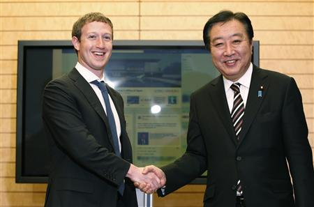 Facebook CEO Mark Zuckerberg (L) shakes hands with Japan's Prime Minister Yoshihiko Noda in front of a monitor displaying a facebook page of the Prime Minister's Office of Japan as they meet at the latter's official residence in Tokyo March 29, 2012. REUTERS/Yuriko Nakao