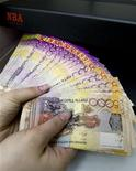 Сотрудник банка проверяет подлинность банкнот казахских тенге в Алматы, 5 февраля 2010 г. Нацбанк Казахстана снизит со 2 апреля 2012 года ставку рефинансирования до 6,5 процента с нынешних 7,0 процентов, сообщил центробанк в четверг. REUTERS/Shamil Zhumatov