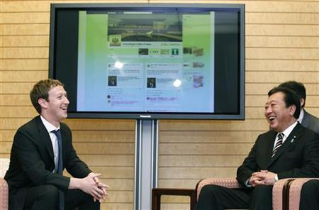 Facebook CEO Mark Zuckerberg (L) shares a light hearted moment with Japanese Prime Minister Yoshihiko Noda in front of a monitor displaying a Facebook page of the Prime Minister's Office of Japan, as they meet at the latter's official residence in Tokyo March 29, 2012. REUTERS/Yuriko Nakao