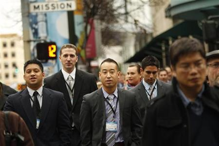 Conference attendees cross a street in San Francisco, California March 15, 2012. U.S. economic growth showed signs of becoming more self-sustaining as the number of Americans claiming new jobless benefits fell back to a four-year low last week and manufacturing activity in the Northeast picked up this month. REUTERS/Robert Galbraith